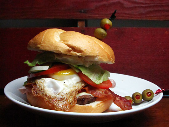 savvyhousekeeping el chivo uruguay sandwich steak, bacon, ham, mozzarella, tomatoes, mayonnaise, lettuce, red pepper, and a fried egg